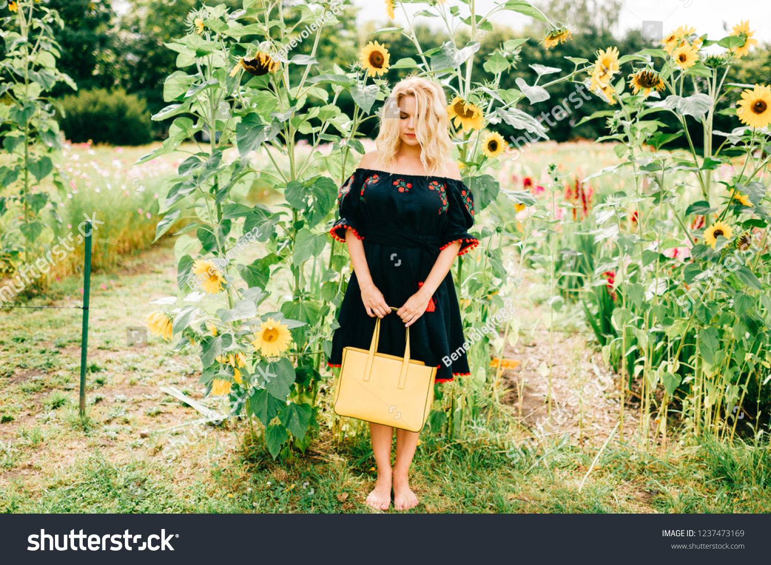 stock photo lifestyle portrait od unusual odd beautiful blonde girl in black embroidery with ornament holding