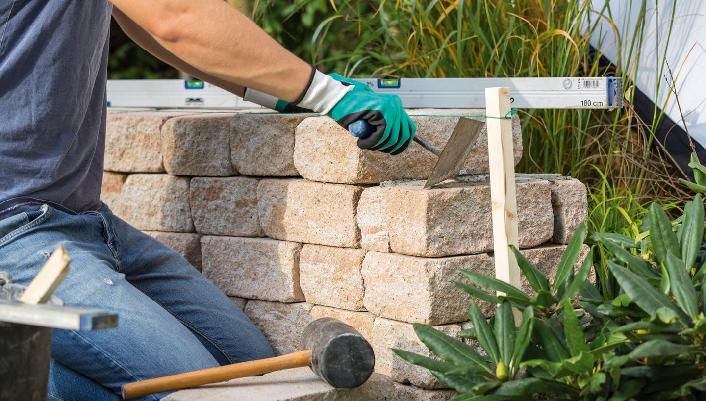 foto heimwerker bau gartenmauer hammer spatel wasserwaage