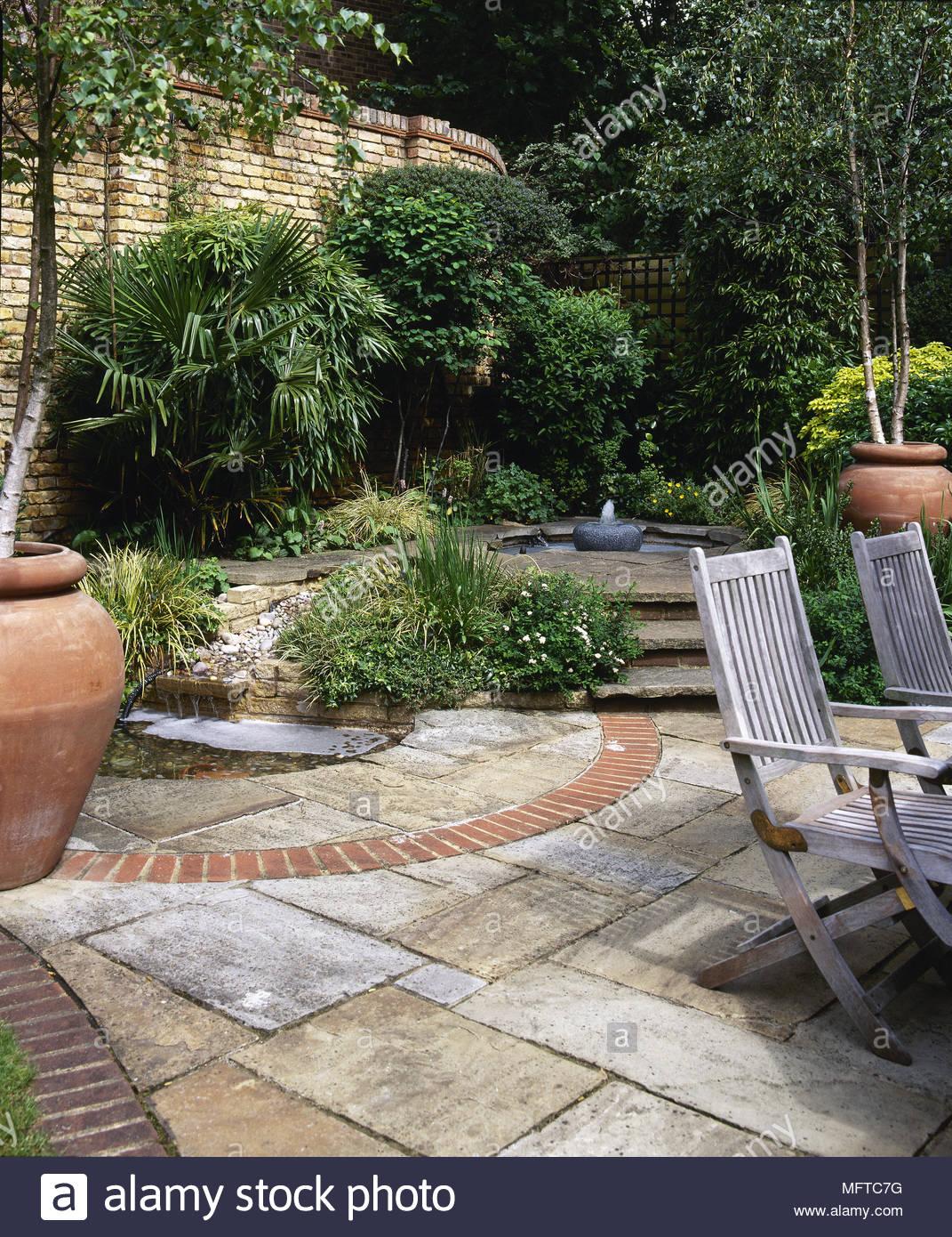 privater garten mit topfpflanzen stein fliesen terrasse und schritte bis zu einem teich mftc7g