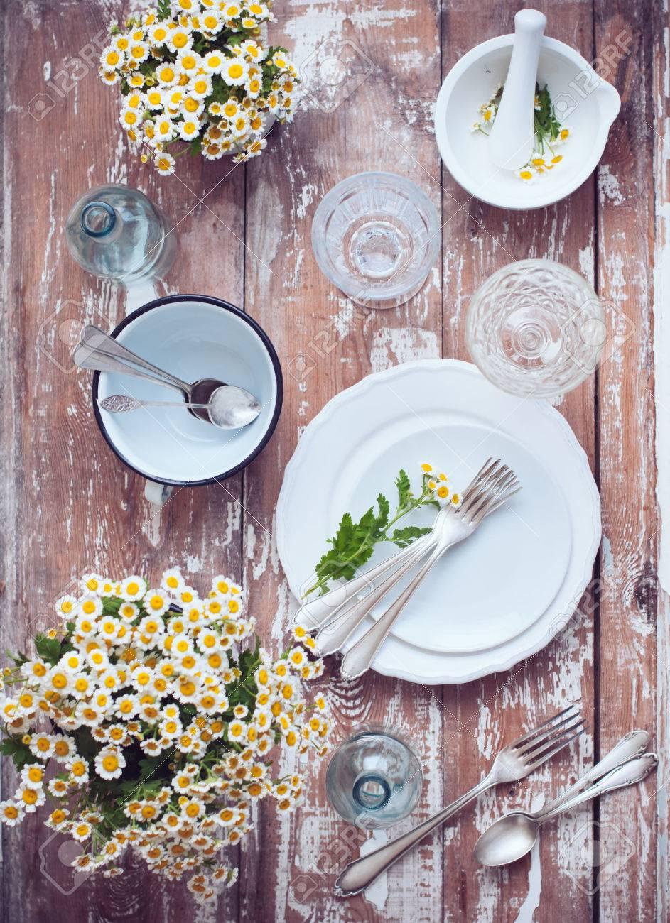 fleurs de camomille laqué blanc ustensiles de cuisine bouteilles en verre couverts de cru sur un fond