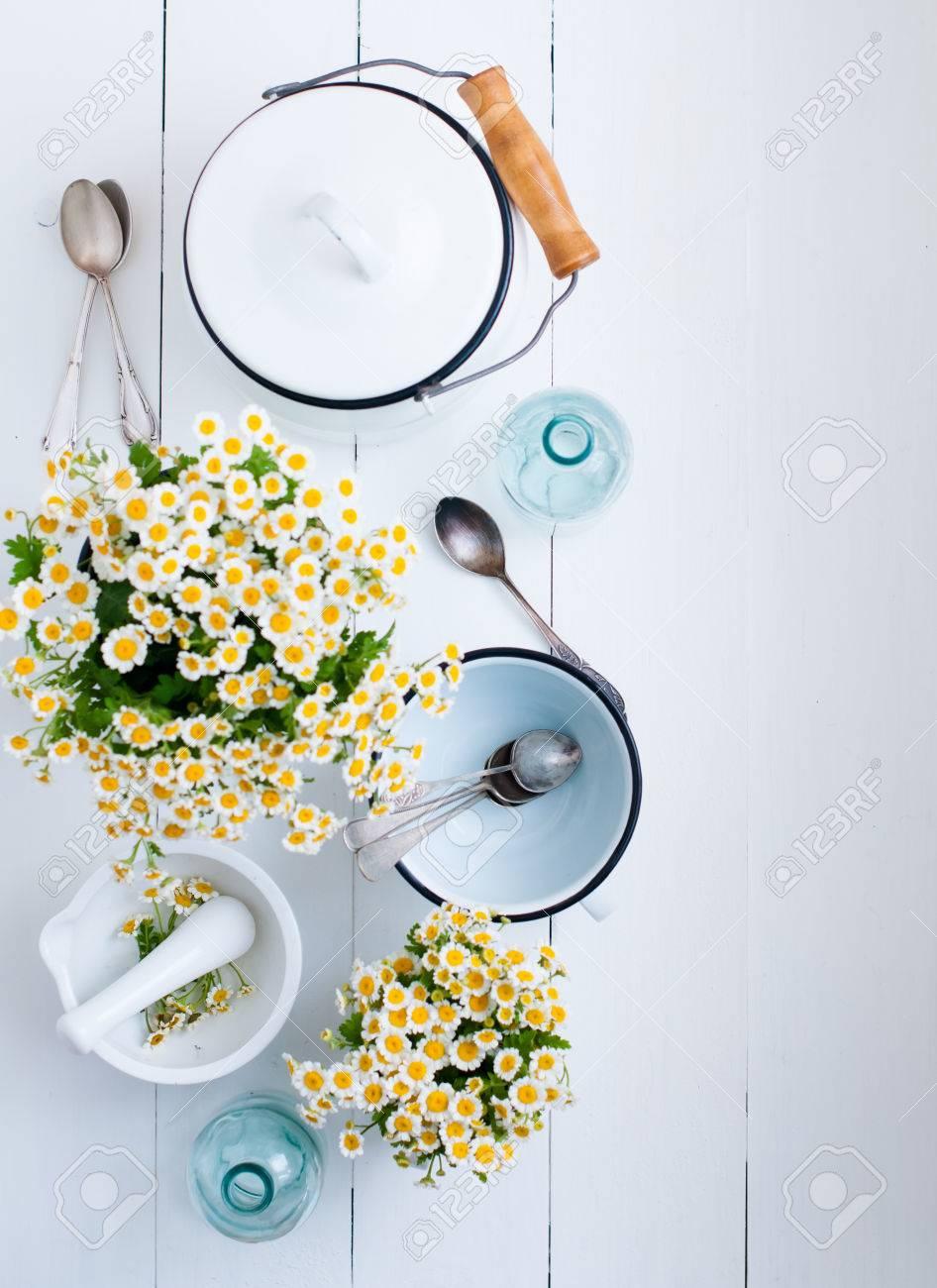 fleurs de camomille laqué blanc ustensiles de cuisine bouteilles en verre des cuillères de cru sur un fo