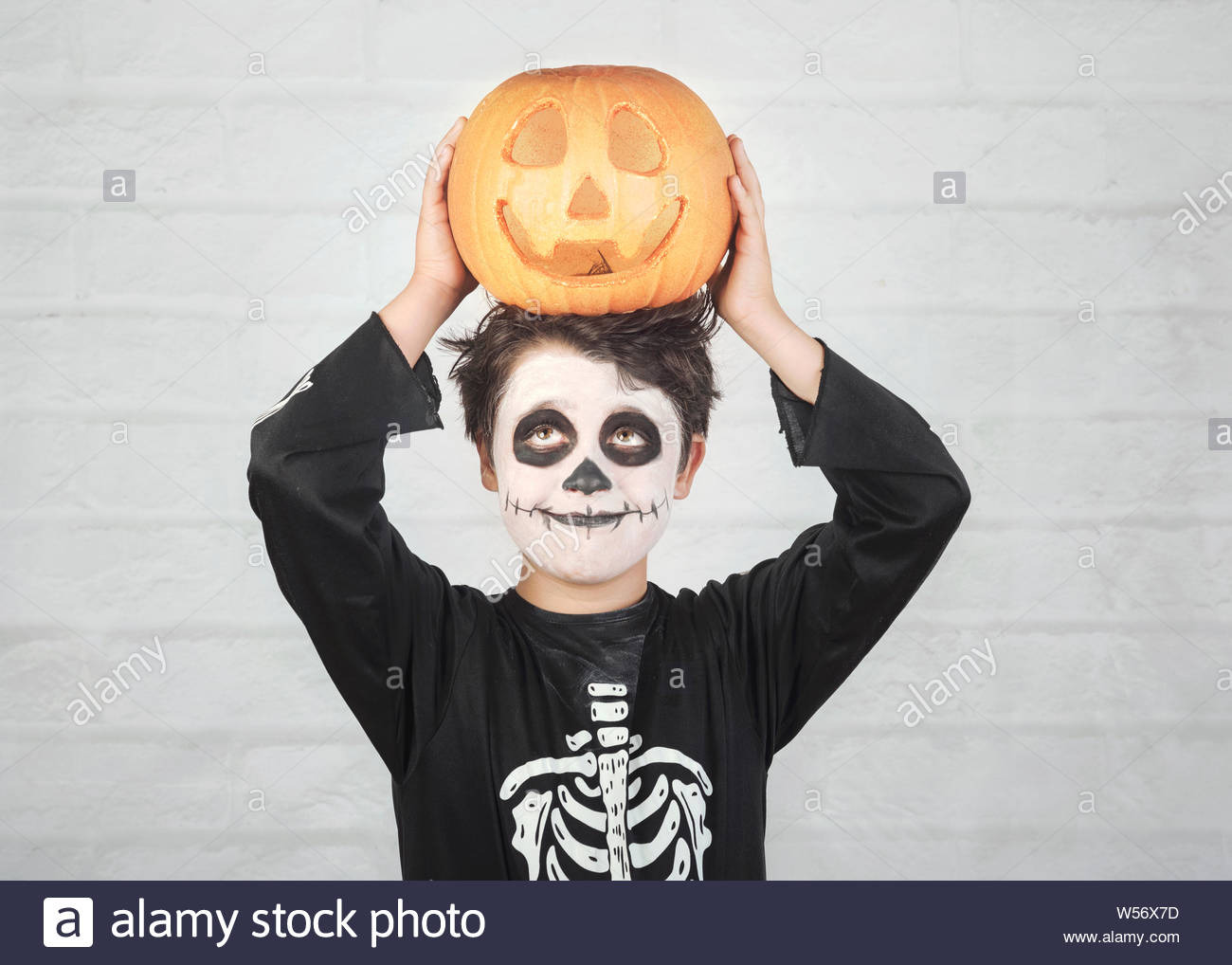 happy halloweenfunny child in a skeleton costume with halloween pumpkin over on his head against brick background W56X7D