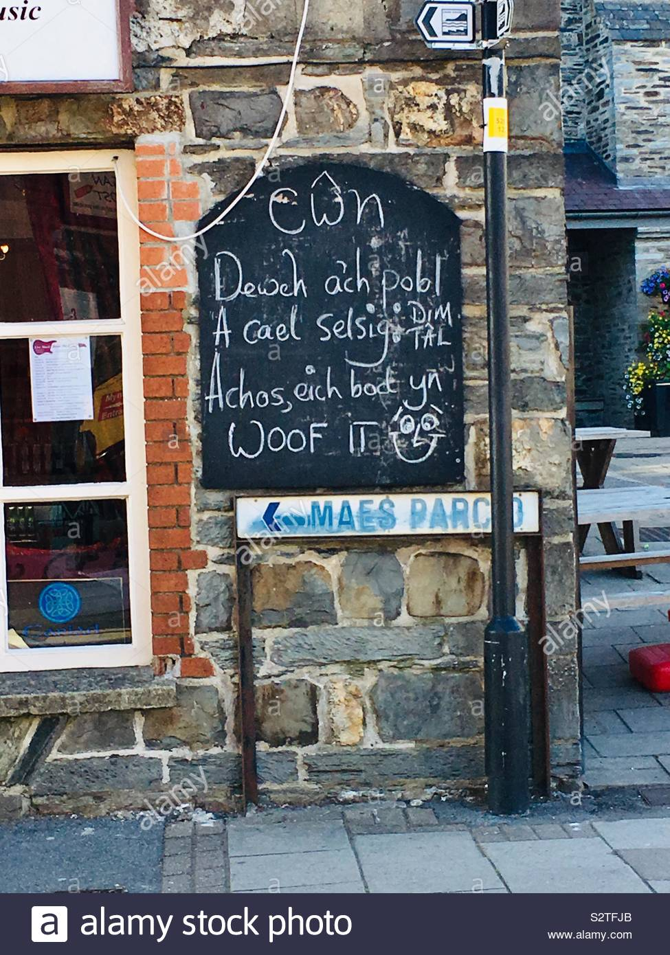 welsh language sign dogs bring your humans a free sausage because youre woof it on a cafe in cardigan wales S2TFJB