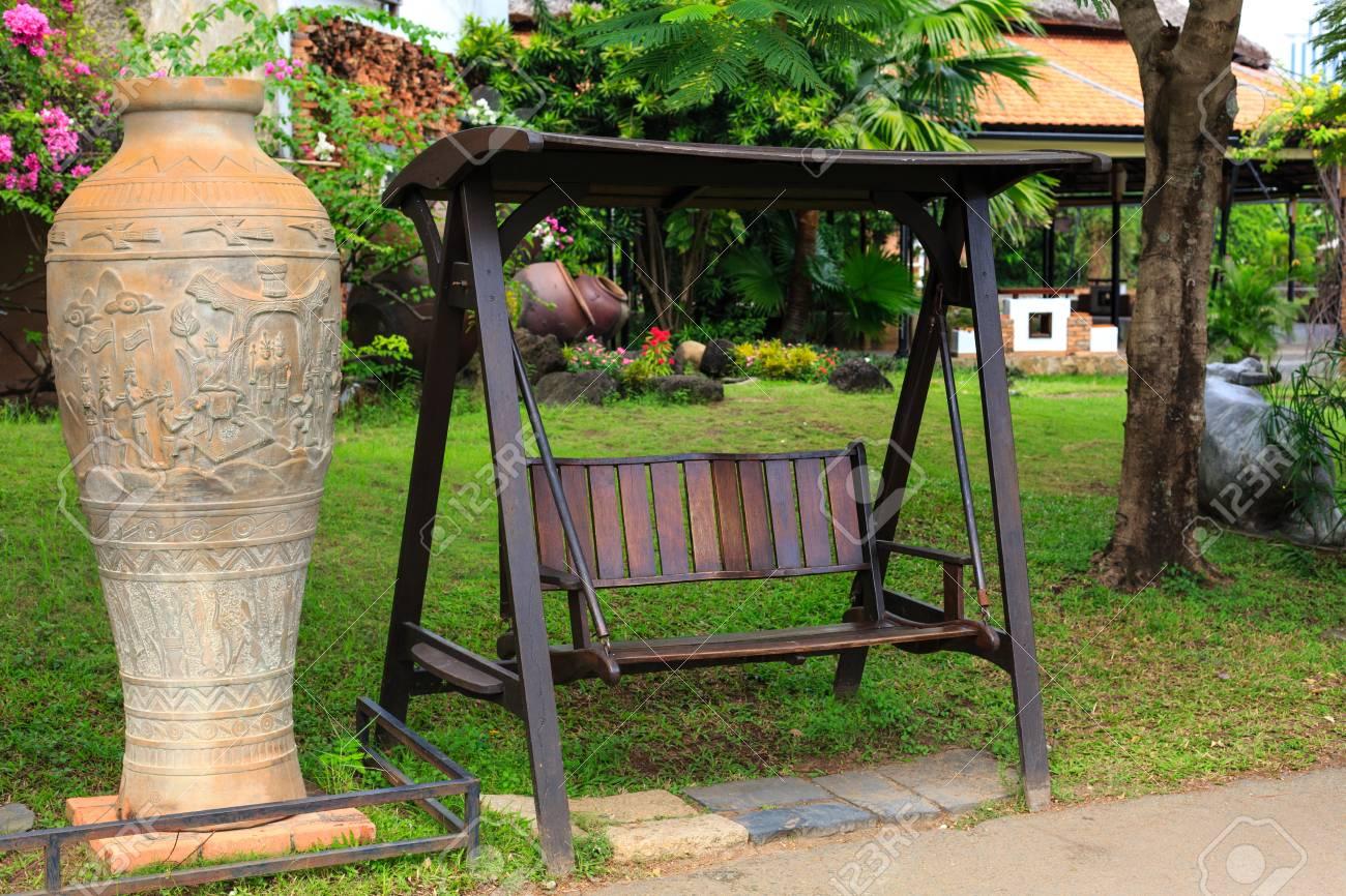eine große keramik vase in den grünen park im freien holzbank schaukel neben