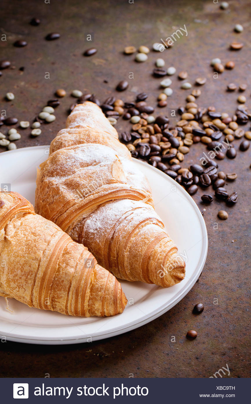 plate with two fresh baked croissants with heap od roasted and unroasted coffee beans over rusty metal background XBC9TH