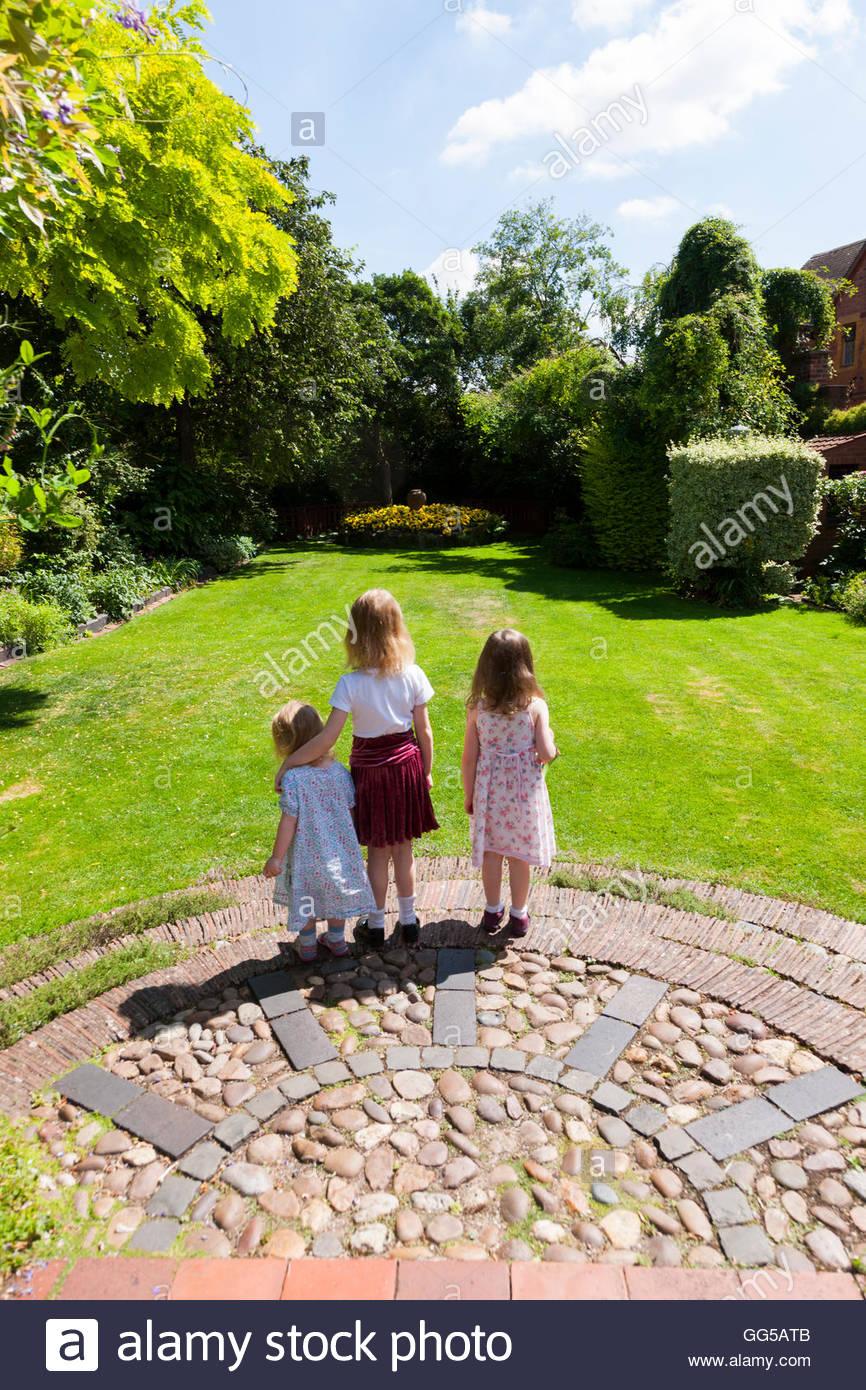 kind drei schwestern 3 kinder kids kind blick auf schone garten laufen spielen auf garten rasengras uberlegen gg5atb