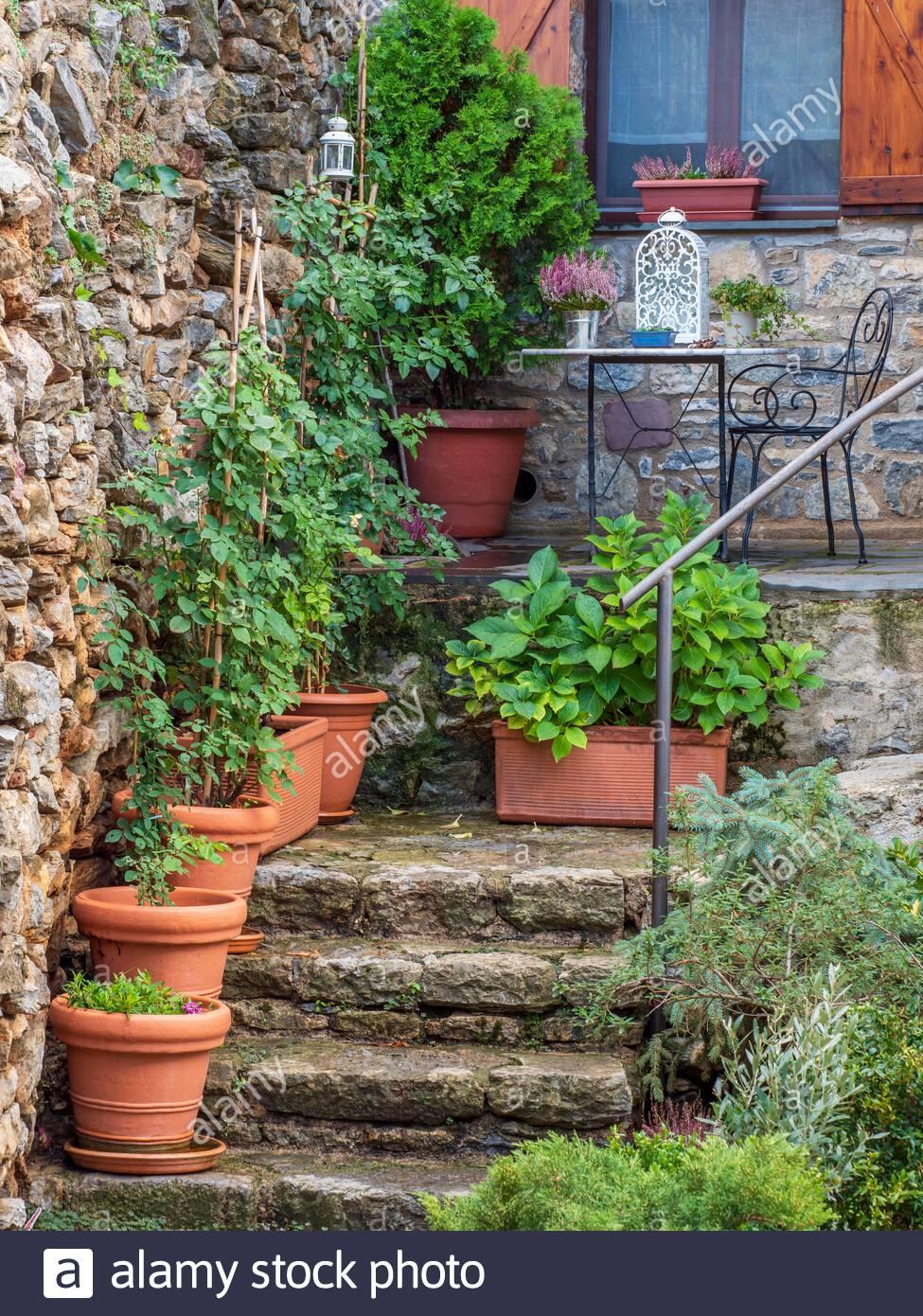 ein garten mit einer naturstein treppe mit blumentopfe eingerichtet mit einer kleinen terrasse uber es und ein fenster mit fensterladen 2ahf7x8