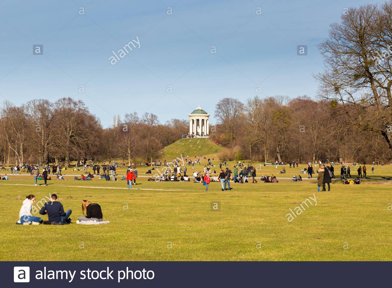 view on the so called monopteros at the english garden englischer garten in the foreground people walking by sitting in the grass popular park 2B45J46