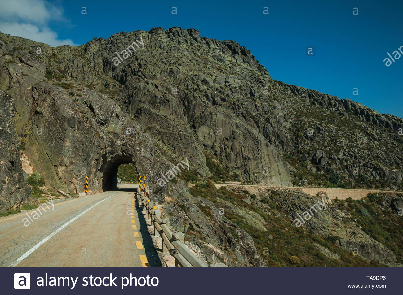 road on hilly landscape passing through tunnel dug in rock at the highlands of serra da estrela the highest mountain range in continental portugal TA9DP6