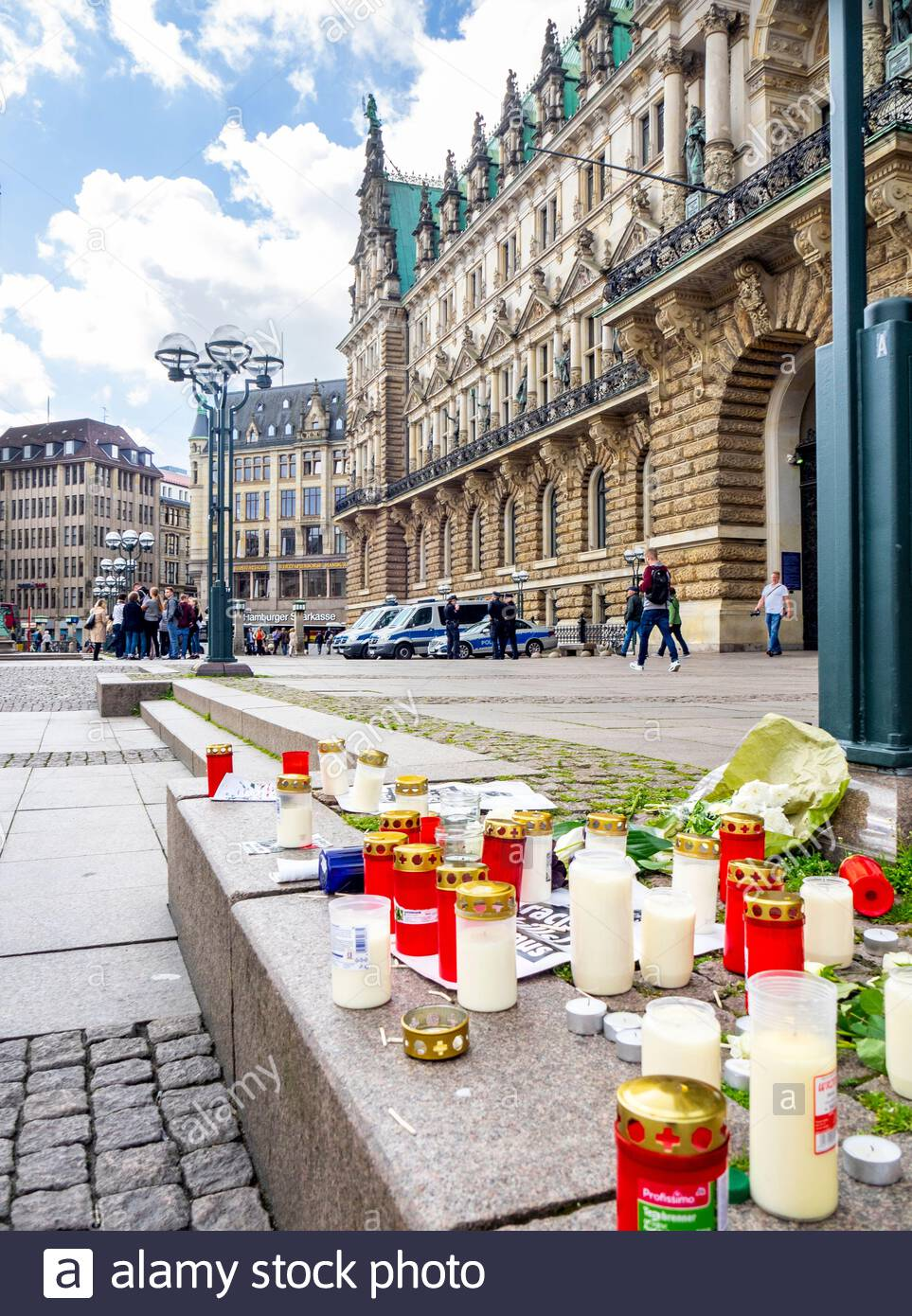 flowers candles and anti racism poster left at rathausmarkt in front of rathaus city hall altstadt hamburg germany 2AE99T8
